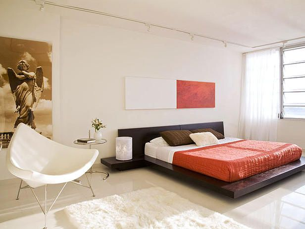 The brown wenge wood king-size bed and pillows are combined with orange bedding and artwork to contrast with the all-white floors, walls, curtains and furniture in this South Beach flat blasted in natural light, facing the Miami skyline beyond.