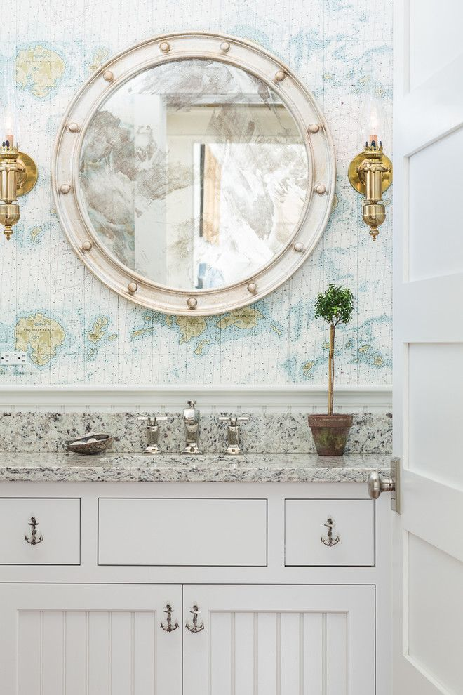 Coastal inspired bathroom with map wallpaper, anchor knobs. granite countertops and round mirror | Spang Builders, Inc.
