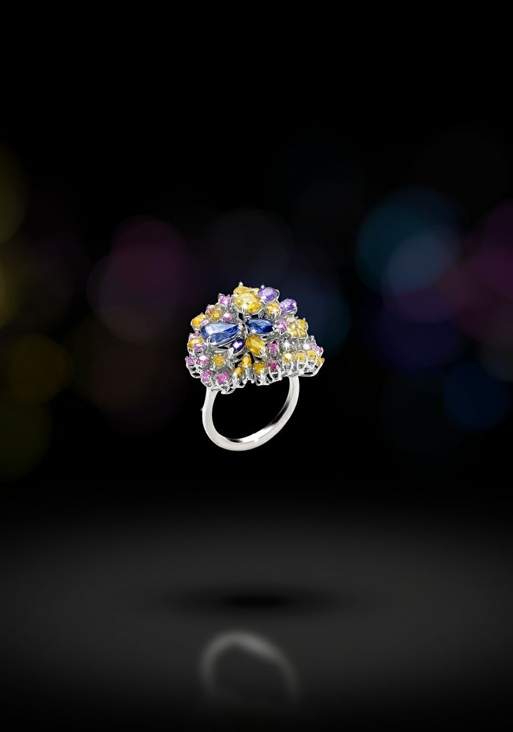 Anello in oro bianco 18 kt contornato da diamanti taglio brillante, zaffiri colorati, ametiste.  (Ring in 18kts white gold with diamonds, coloured sapphires and amethyst. )   Sortija en oro blanco de 18 kt con diamantes, zafiros colorados y amatistas.