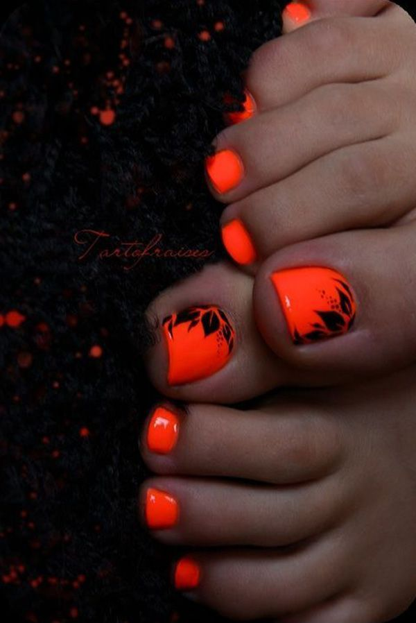 A neon orange and black themed toenail art design. Using neon orange polish as the base color, leaves in black polish are then painted on top to create an illusion of silhouette.