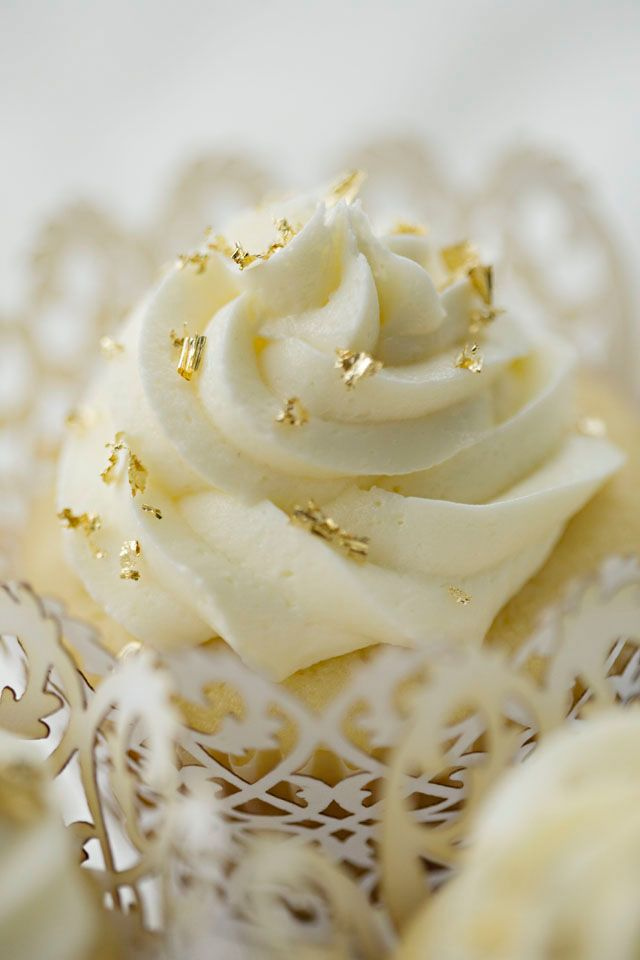vanilla cupcake with white frosting and gold flakes