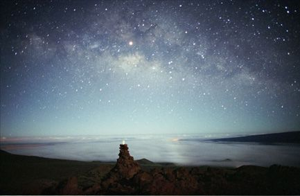 "The Milky Way's cosmic clouds of stars and dust stretch across this picture taken May 2001 from Hawaii. In the foreground is an ""ahu hoku"" - a star marker or star altar - built up of rocks topped with a white piece of coral glowing in the moonlight. Photo by Barney Magrath"