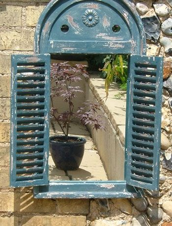 Adding an outdoor mirror creates the illusion of space and doubles the view of your plants and flowers