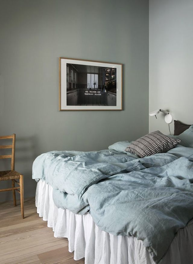 Bedroom with lovely light blue linen and green walls.