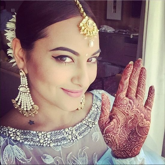 Showing off her mehendi - and that star tattoo.