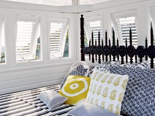 Gothic by the sea: Soft and hard elements combine to define the luxurious simplicity of West Indies style. Here, a palette of black, white, yellow, and blue rests against large white shuttered windows. A dramatic modern Gothic headboard stands out against the peaceful space.