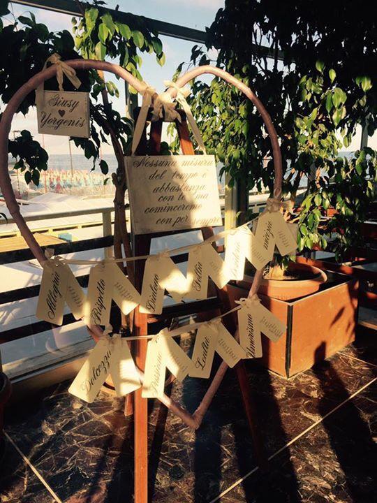 Tableau marriage handmade a forma di cuore con tag invitati e nomi tavolo decorati a mano con tecnica stencil