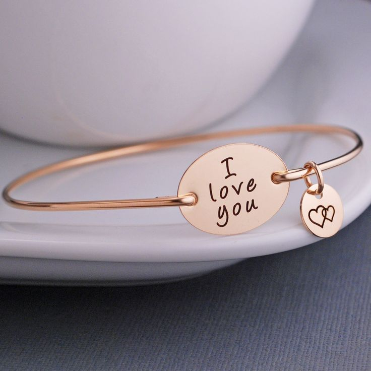 """A 14k gold filled oval measuring 3/4 inch across is engraved with the words """"I…"""