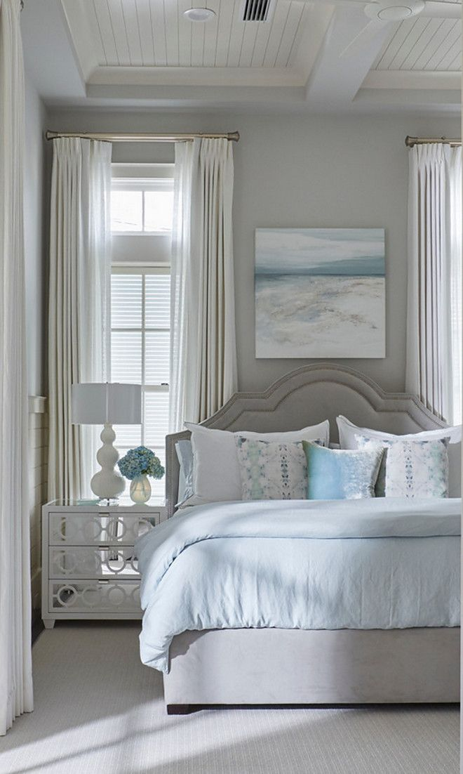This blue and gray guest bedroom features a gray velvet bed dressed in white and pale blue bedding placed next to a white mirrored 3-drawer nightstand. Nightstand is Worlds Away Ava White Lacquer Nightstand. Similar paint color is Benjamin Moore HC-170 Stonington Gray.