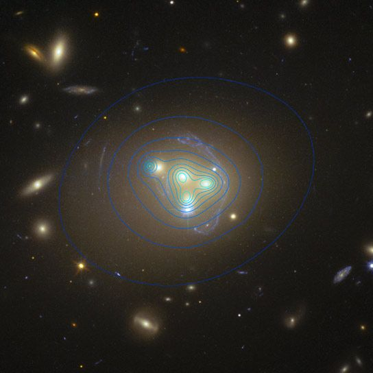 Dark Matter Observed Interacting with Other Dark Matter This image from the NASA/ESA Hubble Space Telescope shows the rich galaxy cluster Abell 3827. The strange pale blue structures surrounding the central galaxies are gravitationally lensed views of a much more distant galaxy behind the cluster. The distribution of dark matter in the cluster is shown with blue contour lines. The dark matter clump for the galaxy at the left is significantly displaced from the position of the galaxy itself,