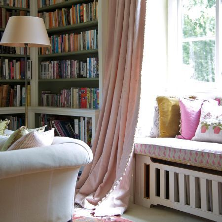 Every library needs voluminous curtains - Susie Watson Designs - Susie Watson Designs Fabric Collection - Plain light pink curtains with a cream sofa, a tall cream floor lamp, and multicoloured window seat and scatter cushions