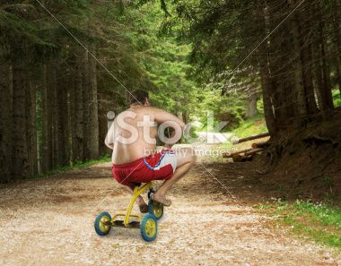 Adult naked man cycling on child's bicycle Photo libre de droits