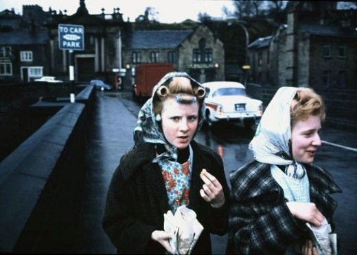 Yorkshire, 1965. John Bulmer. Walking down the street with curlers in, eating chips, classic.