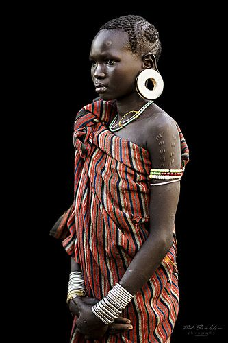 """Young Girl from the Mursi Tribe, Omo Valley, Ethiopia.  The Mursi or Mursu are living in Ethiopia's Omo Valley.  They are well known for their unique lip plates.  They are settled around the Omo River and in the Mago National Park.  Due to the climate, they move twice a year between the winter and summer months.  They herd cattle and grow crops along the banks of the Omo River.  The Series """"African Vogue"""" contains about 300 portraits of tribe members of the Omo Valley in Ethiopia. (Including…"""