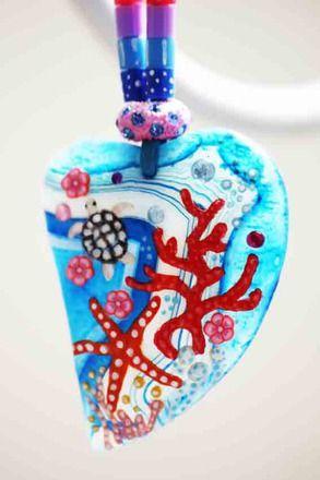 Un petit bout de beauté océane à porter tout contre votre coeur.  Une belle agate translucide (  4cmx5cm ) striée bleue décorée en relief à la main et protégée de plusieu - 20993852