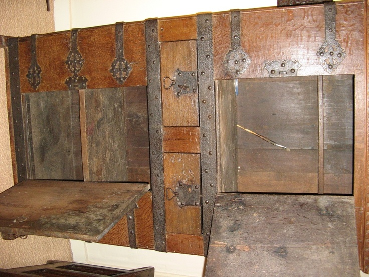 "A 16TH CENTURY WESTPHALIAN OAK AND IRONBOUND STANDING CUPBOARD. CIRCA 1520.    THE CASTELATED TOP ABOVE AN IRONBOUND FRONT CONSISTING OF TWO CUPBOARD DOORS CENTRED BY TWO DRAWERS. ALL ORIGINAL IRON HINGES, LOCKS AND KEYS. WONDERFUL COLOUR AND PATINATION.  40"" WIDE X 69.25"" HIGH X 19"" DEEP."