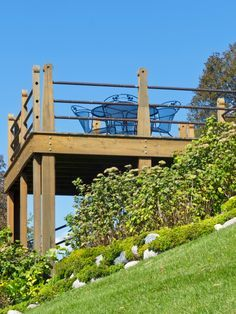Sturdy deck built on steeply sloping hillside with wood and metal railing