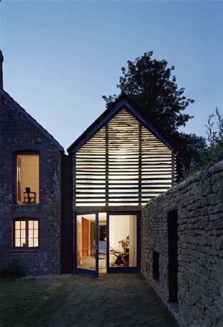Timber skeleton and glass extension filled with light   barn conversion