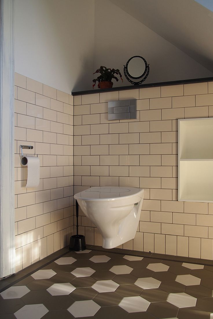 Mindre gästtoalett med kakel i kulören Imperial Ivory samt trvättställ med lavoarkranar, spegel och spegelhylla från Byggfabriken.