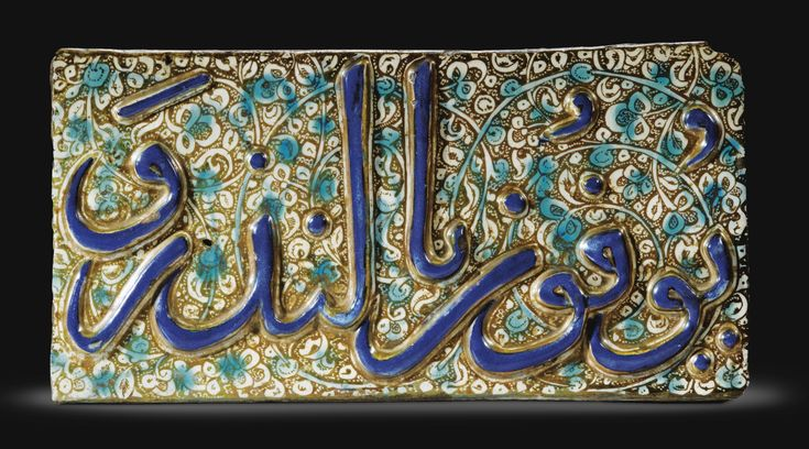 A KASHAN CALLIGRAPHIC LUSTRE POTTERY TILE, PERSIA, END OF 13TH CENTURY the cobalt blue thuluth inscription in relief on a lustre ground with foliate scrolls and turquoise details 20 by 40.5cm.