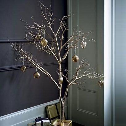 Glam and gold is a fun Christmas look. Add a few choice baubles to a statement twig tree for a bold look. Visit www.redonline.co.uk for more ideas.