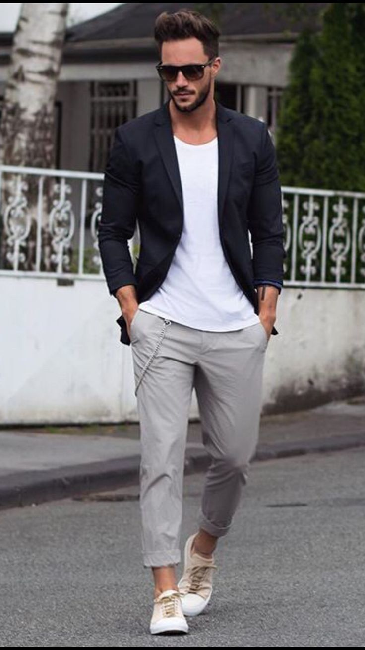 Shop this look on Lookastic:  https://lookastic.com/men/looks/blazer-crew-neck-t-shirt-chinos-plimsolls-sunglasses/13317  — Dark Brown Sunglasses  — White Crew-neck T-shirt  — Black Blazer  — Grey Chinos  — White Plimsolls