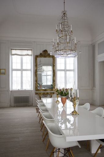 if I owned a castle, this is exactly how i would decorate it. lacquer table and white Eames chairs? LOVE.