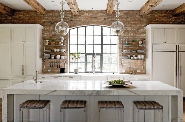 A pair of Baker Christal chandeliers lights up the kitchen. The stools were fashioned from Brace and Black acrylic side tables, with cushions of Lelievre's Zibeline Faux leather. By Designer Julie Dodson.