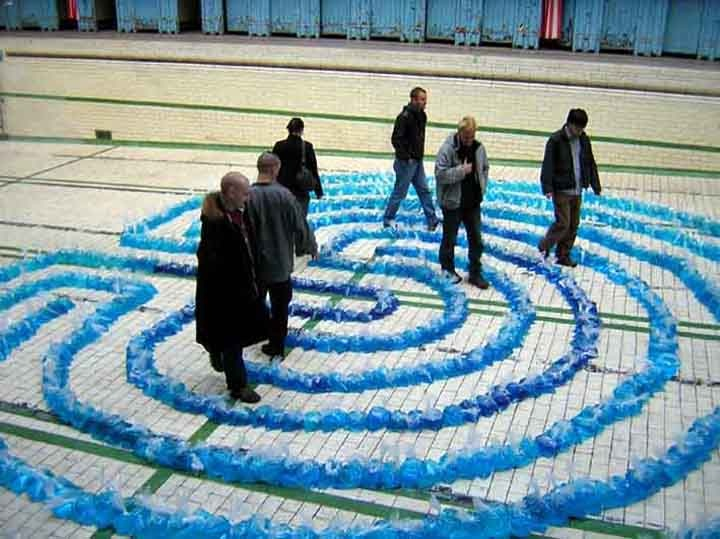 Plastic bags filled with blue water sit on the floor of a swimming pool to create a #labyrinth