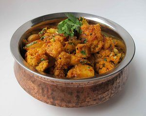 "Perfect aloo gobi: Pop 1ts cumin seed, ½ts nigella seed in 4tb oil; add 350g waxy potatoes (1"" dice). Remove, add 1 med cauliflower (1"" chunks). Remove, add 1 sliced yellow onion, then 4 crushed garlic cloves, 1tb grated ginger. Add 1 tin plum tomatoes, roughly chopped, 2ts ground toasted coriander seed, ½-1ts chilli powder, ½ts turmeric. When oil rises, add potatoes, 2-4 slit green chillies, 1ts salt; after 5min add cauli. Cook til tender, add 1tb methi, 1ts garam masala, then 