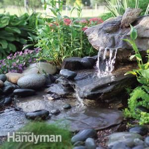 How to Build a Low-Maintenance Water Feature - water fountain flows from rock, no pond so no water maintenance - GREAT idea, I want one near the front door! - Family Handyman #pondless #water #fountain #diy
