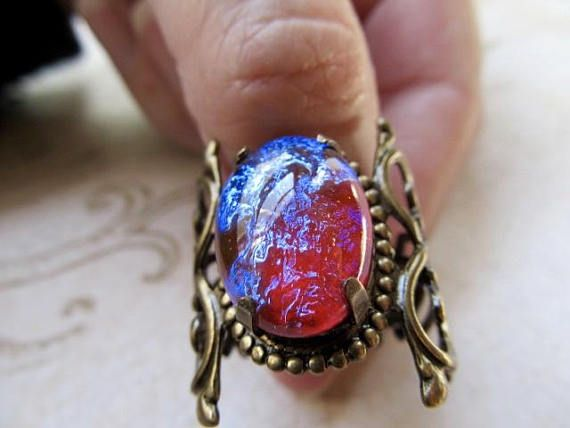 A large red dragons breath opal ring for men, that has complex colors of a fiery warmth of ruby red with shifting colors of cool purple and blue flashes in the bright light and with every move. The band is brass filigree with a celtic design. Giving it as a gift? Dont know what size? This ring is versatile since it is adjustable, you can wear it on any finger you choose or you can wear it as a knuckle ring or pinky ring too. Great for Cosplay or anytime, its Valiant! *The band measures…