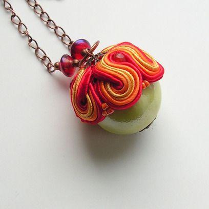 Naszyjnik wykonany metodą haftu sutasz, utrzymany w odcieniach zieleni, czerwieni i pomarańczu. sutasz połączony z ceramiczną kulą , szklanymi koralikami i naturalnymi kamieniami (fasetowany karneol). Główny element stanowi duży (ok 2,5cm średnicy) ceramiczny koralik  w odcieniu jasnej zieleni. Całość zawieszona na łańcuszku w kolorze miedzi. Dla kobiet lubiących się wyróżniać, na pewno nie pozostanie niezauważony. Bez zapięcia, długość łańcuszka ok 68 cm, zawieszka ok 5 cm długości.