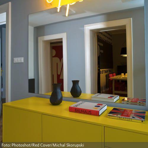 Ein großer Wandspiegel im Flur ist nicht nur super praktisch, da man in diesem vor dem Verlassen der Wohnung oder dem Betreten anderer Räume sein Aussehen überprüfen kann, sondern auch, weil er den Flur durch die Spiegelung optisch vergrößert. Zusammen mit der gelben Kommode im Flur und der witzigen Leuchtschrift entsteht ein modernes und junges Raumkonzept.
