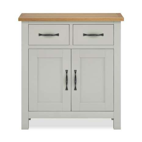 Offering two drawers and a two door cupboard with curved metal handles, this fully assembled small sideboard is crafted from cotton painted oak with an oak vene...