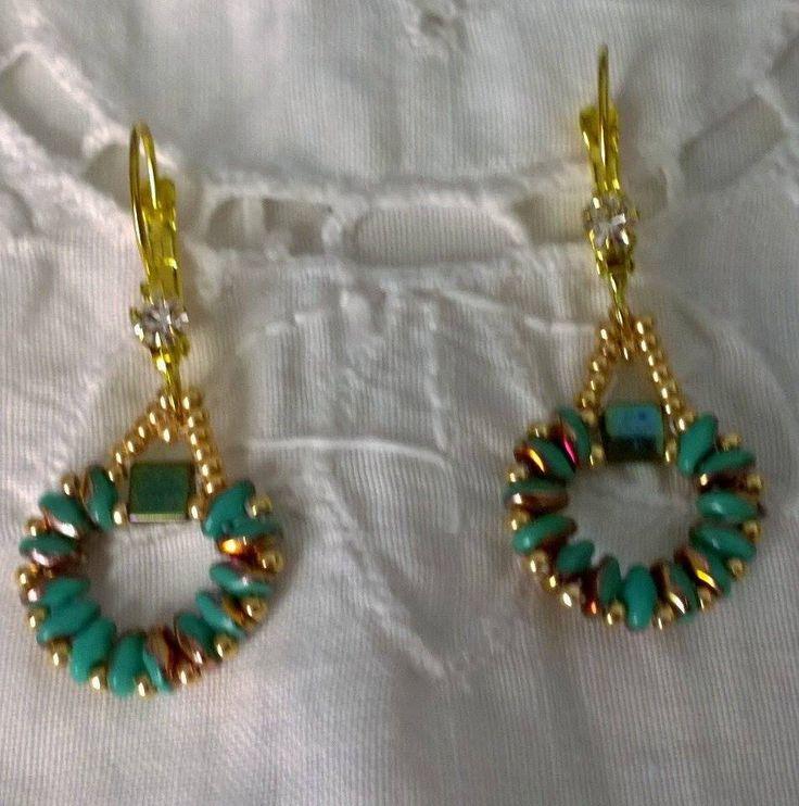 Orecchini realizzati con la tecnica della tessitura delle perline. Nei toni del turchese e dell'oro di piccole dimensioni con conteria e Tila di Boemia. Gancio con strass.