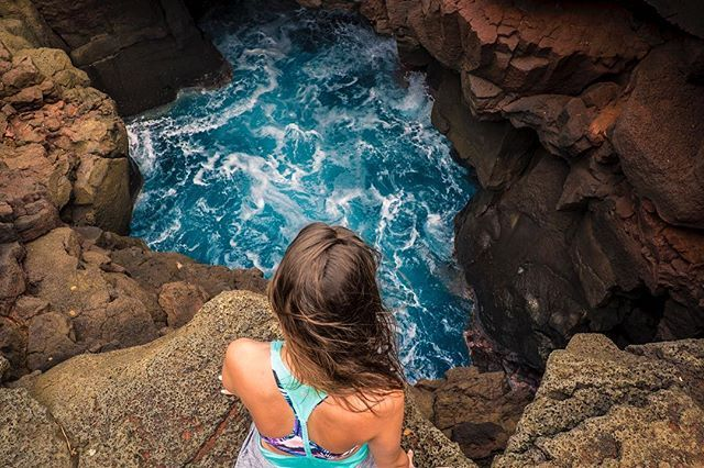 Happy Monday InstaFam!  .   Here I am peering into the cave at Ka Lae (South Point) on the Island of Hawaii.  You can cave jump or cliff jump here if you dare! Its also the most southern point of Hawaii and of the United States  .   The 12 meter drop didnt look as high as the pictures but the rain and high winds stopped us from taking the leap during our visit   Check out Day 8 in our story highlights for behind-the-scenes  .   We want to know.... would you jump in?!  .   We just finished…