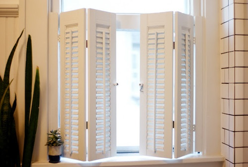 """""""We found these shutters at a thrift store for $4. Two coats of paint and some hinges later and they're perfect for our vintage bathroom,"""" she says."""