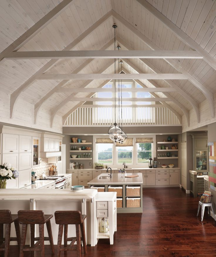 Raised door panels and open shelving in light colors, plus dramatic light fixtures, draw the eyes up to a vaulted ceiling in this spacious and sophisticated kitchen.