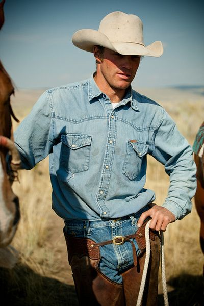 This is classic cowboy style at its best: Denim shirt, Levis, chaps and a cowboy hat.