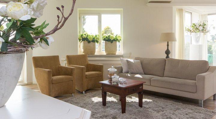 Een naturel kleurenpalet zorgt voor rust. Een paar grote tafellampen en bloempotten (ipv veel kleine items) versterken dat nog eens.