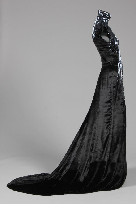 An Alexander McQueen black velvet and bugle beaded evening gown, 'In memory of Elizabeth Howe, Salem 1692' collection, Autumn-Winter, 2007, the iridescent gun metal-blue beading forming a star-burst around the high neck and upper shoulders which descend and trail down the front of the skirt trained skirt.