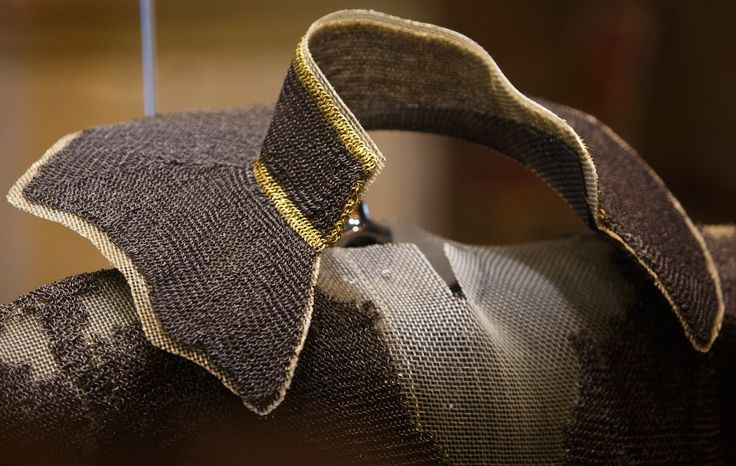 St. Wenceslaus (Vaclav) hauberk, the oldest known complete European riveted mail hauberk, 1st part of the 10th c, detail view of the collar showing the solid gold links, alternating round riveted and solid (punched) rings, the wire is said to be 0.75 mm in dia., with an inner dia. of 5-6 mm (external dia. of 6.5-7.5 mm). The rings are worn, with numerous repairs, the wire might have originally been about 1mm in diameter, the church treasury of St. Vitus Cathedral in Prague, Czech Republic.