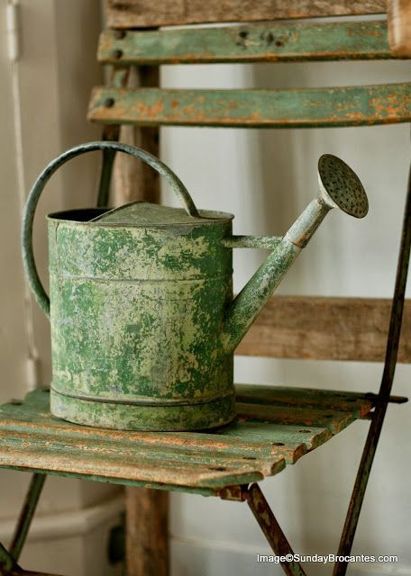 Chippy, green watering can on a chippy, green folding chair.