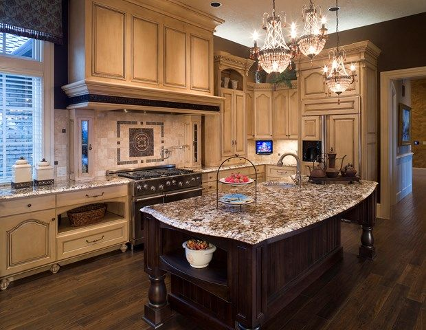 Traditional kitchen with a brand new granite island with dark wood, a beautiful backsplash and beige cabinets all around. #DIY