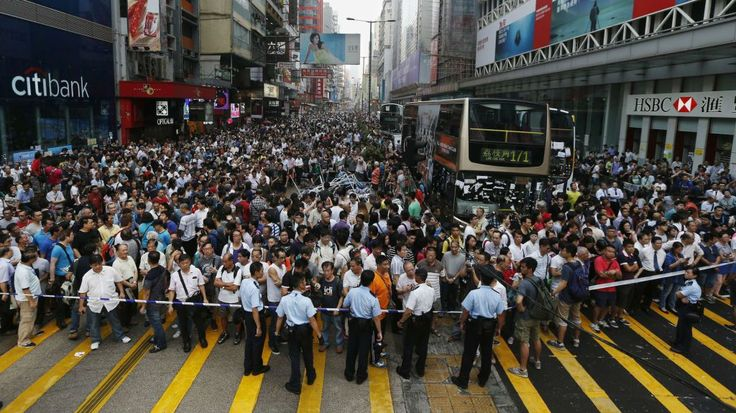 Anti-Occupy Central protesters stand behind a police cordon on Nathan Road at a pro-democracy protest site in Mongkok, Hong Kong.