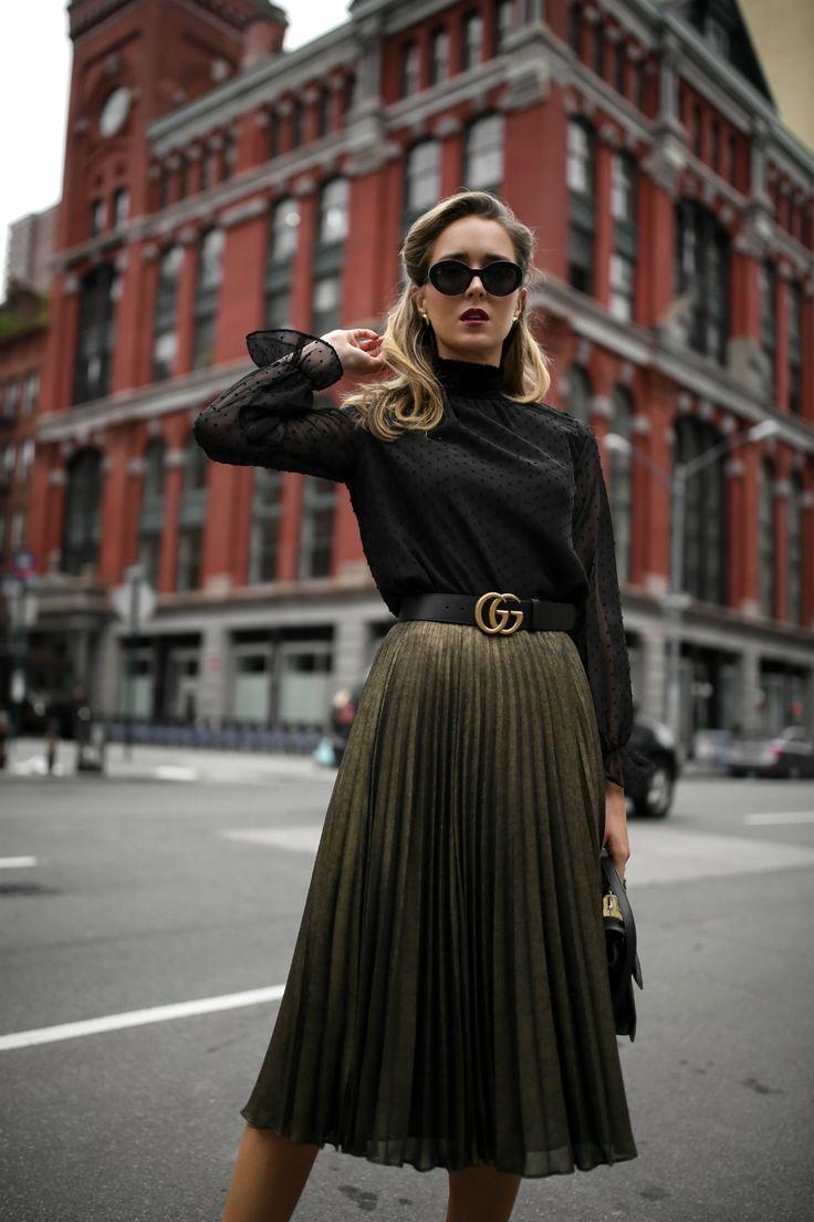 Mary Orton of Memorandum wears a Hobbs London metallic pleated midi skirt, a black Aqua mock neck blouse with Swiss-dot detailing, a black leather Gucci waist belt and black cat eye sunglasses