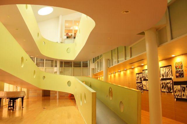 建物の中心の吹き抜けには淡いグリーンのスロープ。3階までの部屋をすべてつないでいる