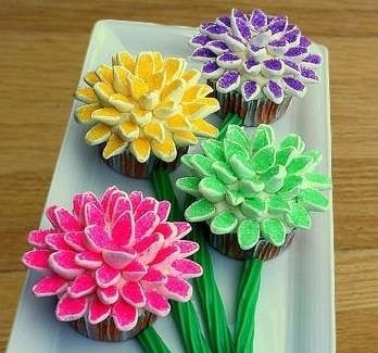 Cut mini marshmallows in half diagonally. Put in plastic bag with decorative sugars. Shake. Sugar only sticks to cut part. Let them sit and petals will puff up again. Attach with icing on cupcake.
