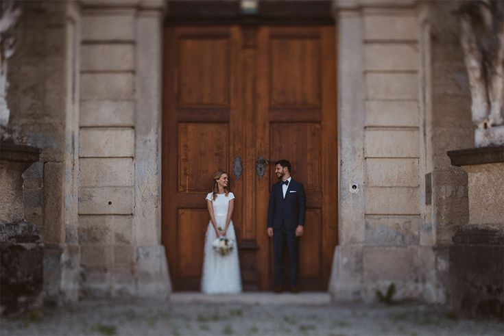 I Love this photo of the couple standing in front of the big door, while looking at each other.